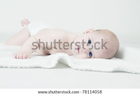 Cute baby lying on white blanket - stock photo
