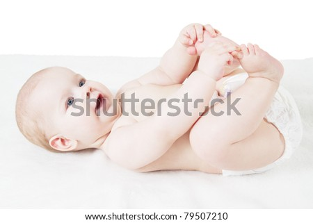 Cute baby lying on white blanket and holding legs - stock photo