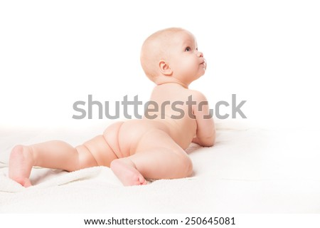 Cute baby lying on white blanket on stomach, knee bent. Isolated over white background. - stock photo