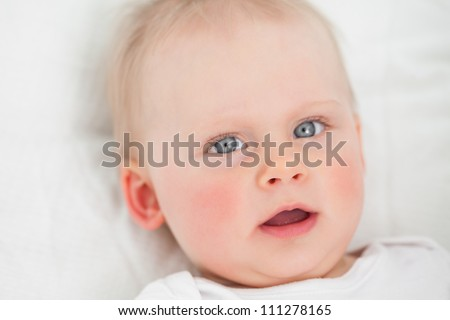Cute baby lying while opening her mouth indoors - stock photo