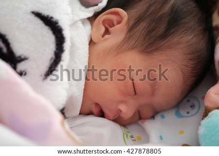 Cute baby of two days old newborn girl , close-up portrait