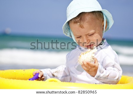 cute baby on a beach and playing with his toy