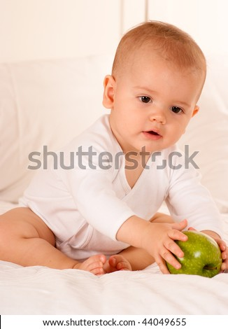 Cute baby on a bodysuit reaching for a green apple - stock photo