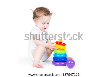 Cute baby playing with a plastic pyramid - stock photo
