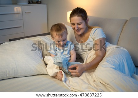 Cute baby playing with doll on bed with mother