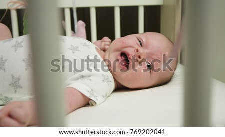Cute baby playing with feet in baby crib