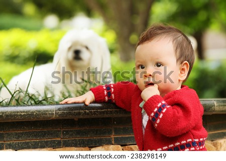 Cute Baby Playing with her Dog Outside in the Garden - stock photo