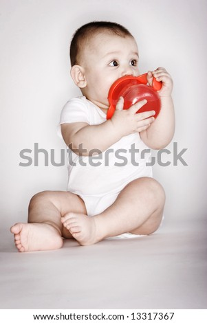 Cute baby playing with his sippy cup - stock photo