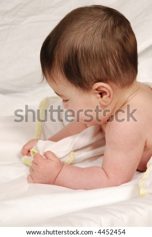 cute baby playing with towel - stock photo