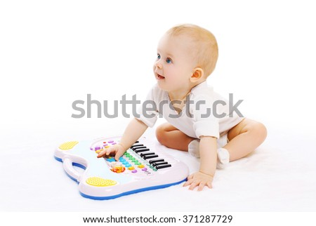 Cute baby playing with toy piano on a white background - stock photo