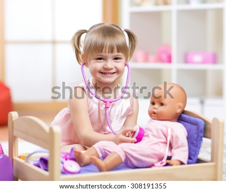 cute baby plays in doctor with toy doll and stethoscope - stock photo