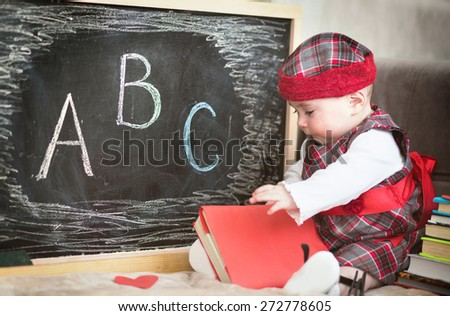 Cute baby plays with book and glasses - stock photo