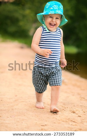 Cute baby running on the beach outdoors - stock photo