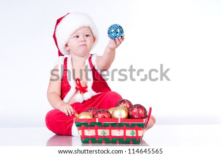 Cute baby Santa Claus with garlands and a basket of Christmas toys - stock photo