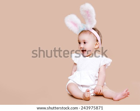 Cute baby sitting in costume easter bunny - stock photo