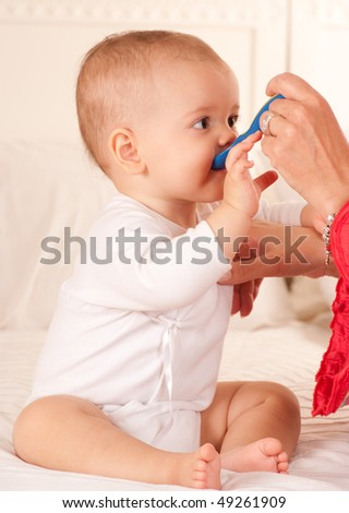Cute baby sitting on a bed being fed with a plastic spoon - stock photo