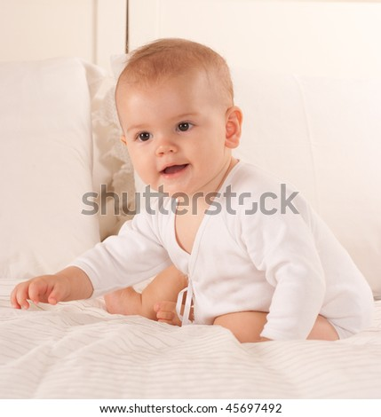 Cute baby sitting on a bed dressed in a bodysuit - stock photo