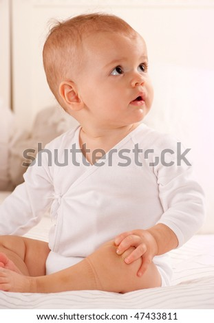 Cute baby sitting on a bed dressed in a bodysuit