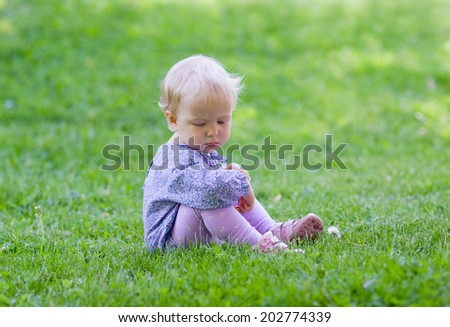 Cute baby sitting on a meadow, green grass, summer