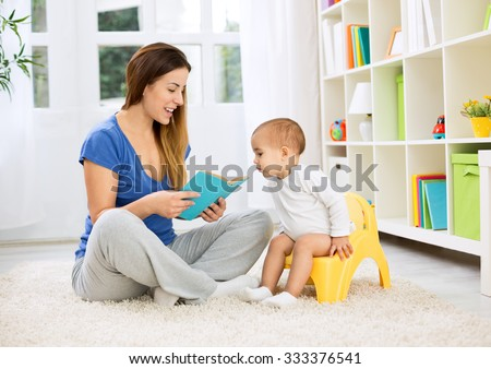Cute baby sitting on bedpan and listening kid story with mom - stock photo