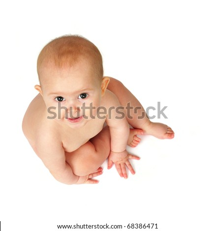 Cute baby sitting on floor and looking up at camera.