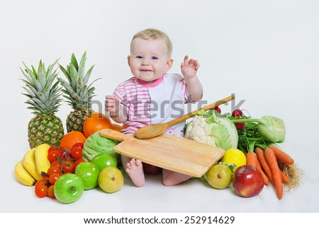 Cute baby  sitting with fruits and vegetables and hold an apple isolated on white background. Concept: healthy vitamin vegetable food diet make baby strong and happy - stock photo