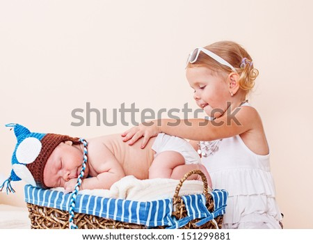 Cute baby sleeping in a basket and a toddler girl - stock photo
