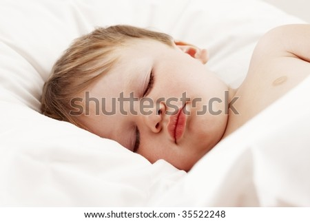 Cute baby sleeping in bed - stock photo