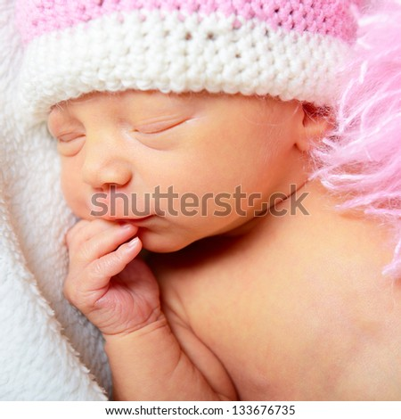 cute baby sleeping in funny pink hat, beautiful kid's face closeup - stock photo