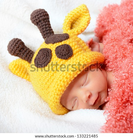 cute baby sleeping in  hat and smiling in sweet dreams, beautiful kid's face closeup - stock photo