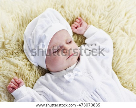 Cute baby sleeping on a sheep fur. Beautiful dreaming baby with white dress and cap. Close-up shot.