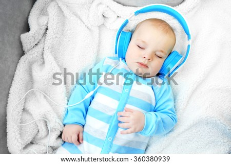 Cute baby sleeping with headphones on comfortable sofa in the room, close up - stock photo