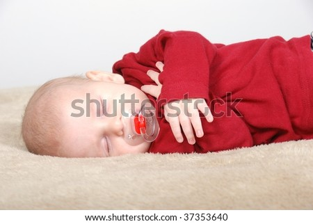 Cute baby sleeping with pacifier - stock photo