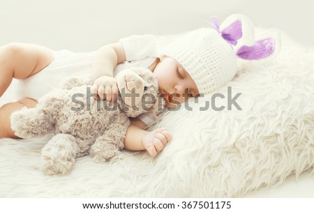 Cute baby sleeping with teddy bear toy on white soft bed at home - stock photo