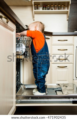 Cute baby standing on dishwasher in kitchen and helps it unload