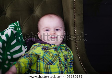 Cute baby toddler sitting on a green armchair near white checkered pillow, fool around, portrait - stock photo