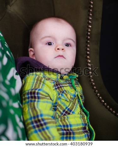 Cute baby toddler sitting on a green armchair near white checkered pillow, serious - stock photo