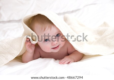 cute baby under a white towel - stock photo
