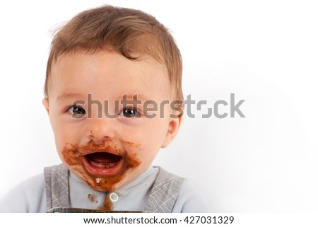 Cute baby very happy after eating chocolate.