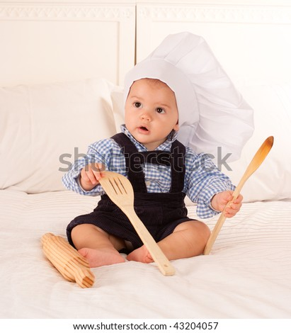 Cute baby with a cook hat playing with a rolling pin and wooden spoons