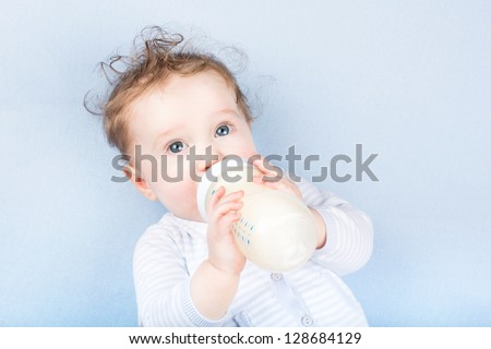 Cute baby with a milk bottle on a blue blanket - stock photo