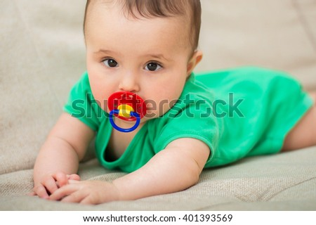 Cute baby with a pacifier - stock photo