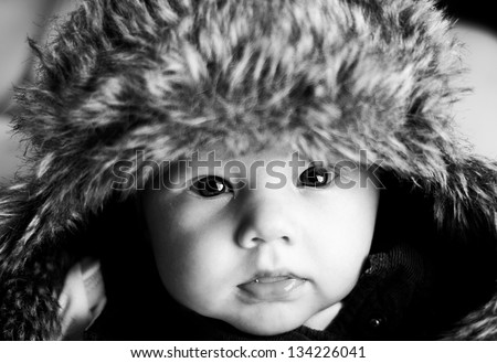 Cute baby with adults hat, black and white - stock photo