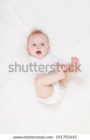 Cute baby with beautiful blue eyes lying in white bed