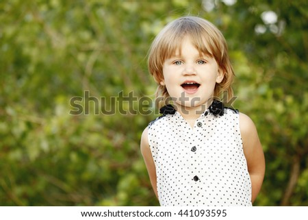 Cute baby with blonde hair. Little girl 2-3 year old. Lifestyle, outdoors - stock photo
