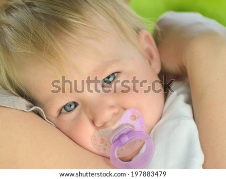 Cute baby with blue eyes cuddles up in her mother's arms. - stock photo