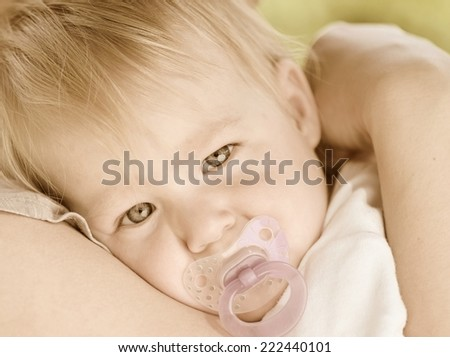Cute baby with blue eyes cuddles up in her mother's arms. Vintage style.