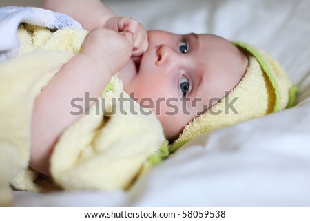 Cute Baby with blue eyes on a white bed with a yellow towel around her body after bathing. baby is very sweet and cute. she is sucking on her right hand at her small thumb. - stock photo