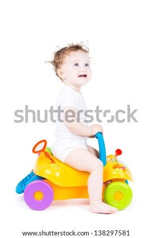 Cute baby with curly hair on a toy car - stock photo