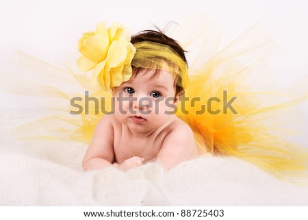 cute baby with dark hair and yellow ribbon with flower